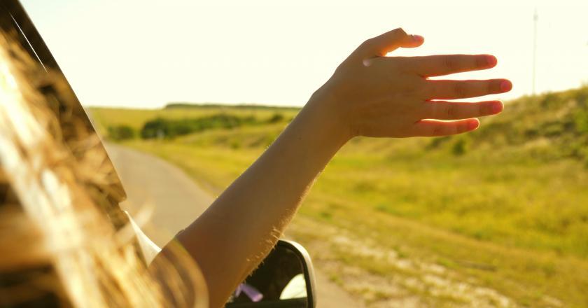passager en voiture avec la main dehors