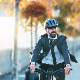 Homme sur vélo casque et cravate